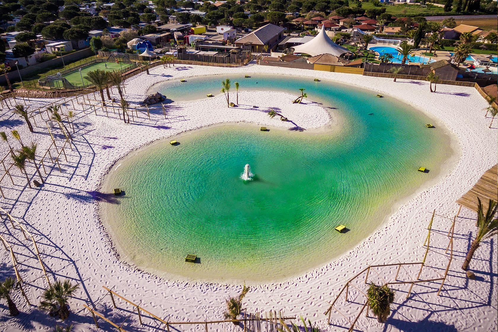 La playa de arena y la zona de la piscina de la laguna