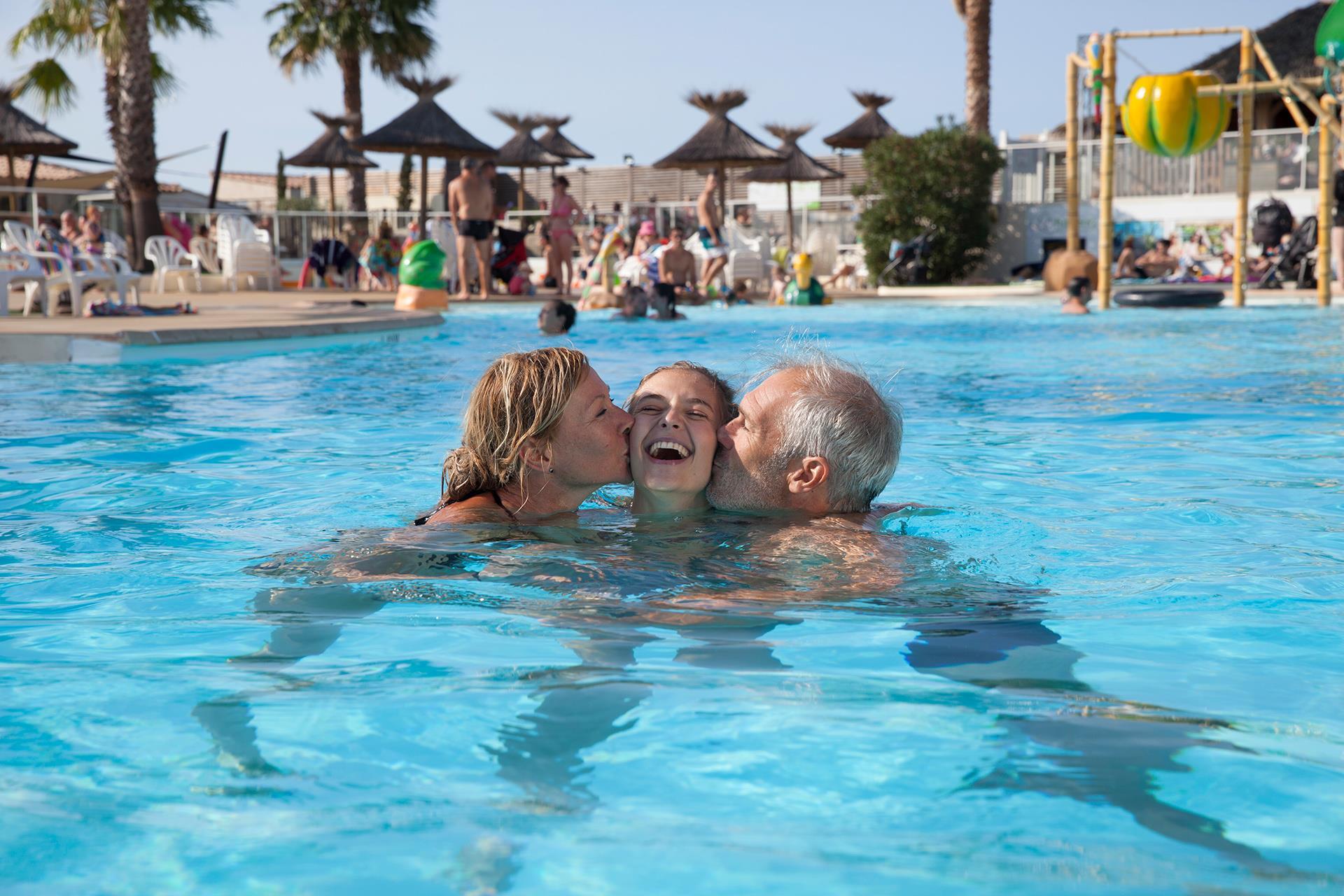 Schwimmbad Familie Pool Sonnenschirme Palmen