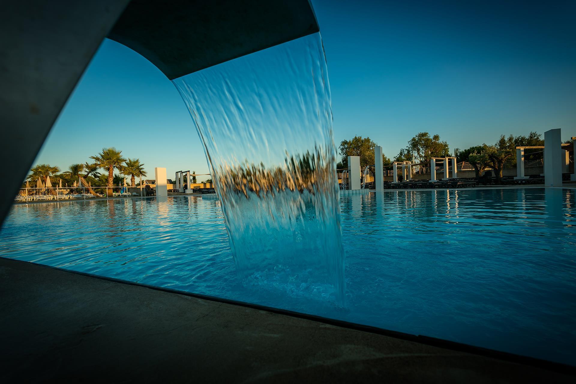 gran piscina cascada palmeras relajarse