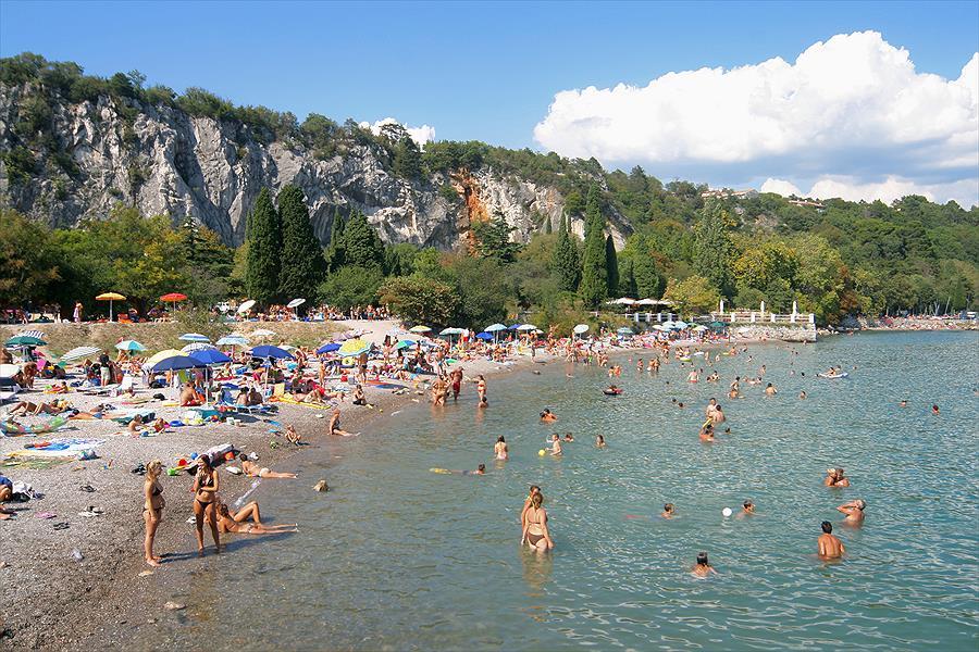 strand zee rotsen natuur groen zwemmen baden parasols