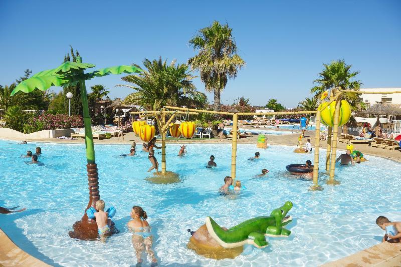 Parque acuatico Piscina para bebes Palmeras Vacaciones familiares Tumbonas